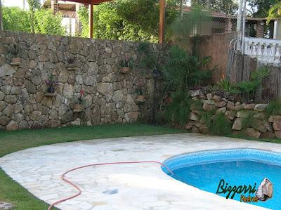 Construção de piscina em residência em Mairiporã-SP com o muro de pedra, o piso com pedra caco de São Tomé e a execução do gramado com grama esmeralda.