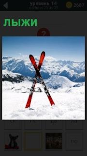 В снегу крест на крест стоят лыжи в сугробе и вдали видны заснеженные горы