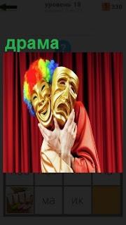 Перед занавесом человек держит две маски в руках, указывающие на драму в постановке