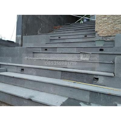 Pemasangan batu andesit pada lantai tangga