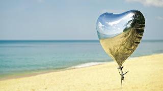 Zilveren ballon op het strand in de zomer.