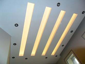 Üzerinde üç uzun sarı loş aydınlatma olan küçük kartonpiyer asma tavan