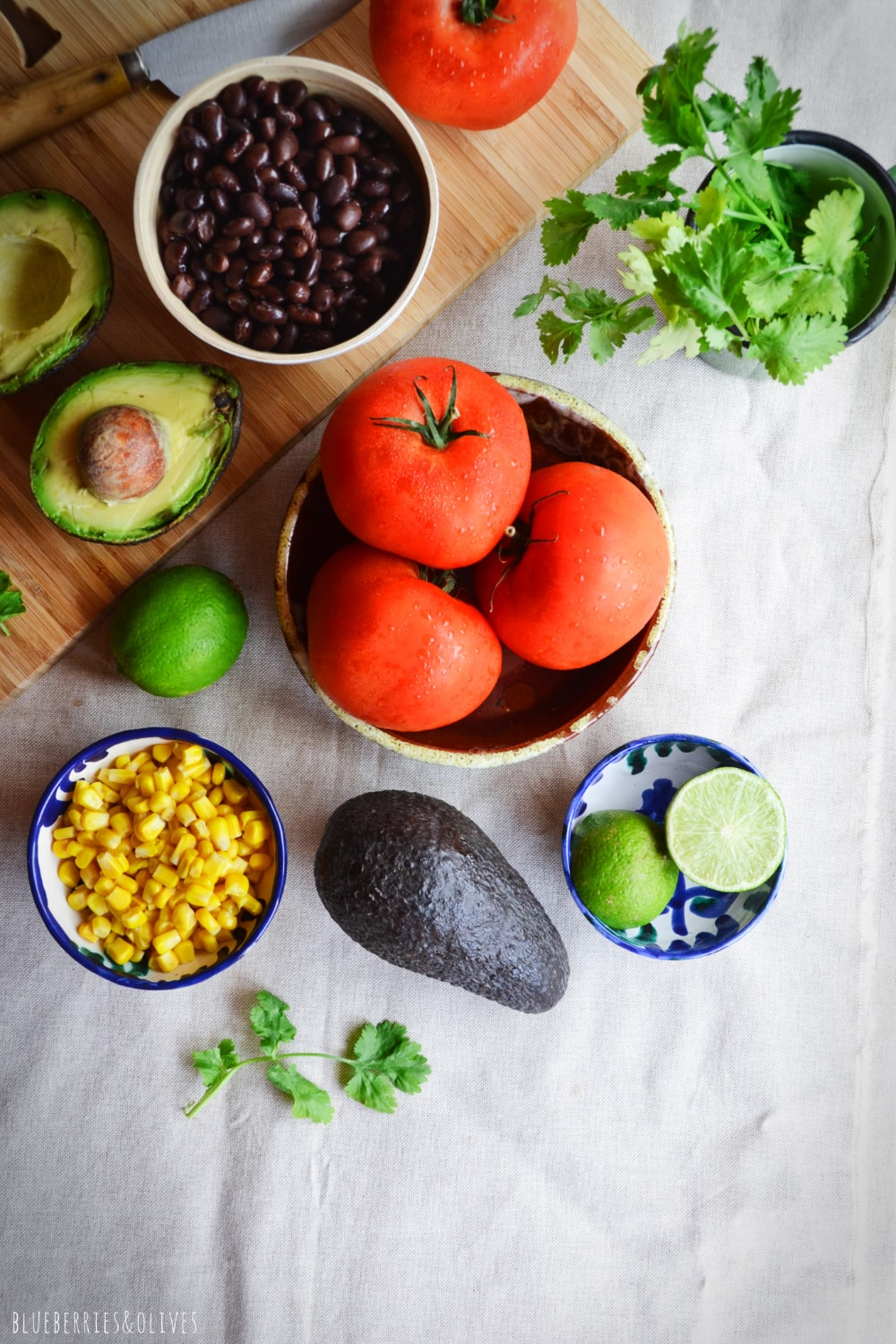 INGREDIENTS STUFFED TOMATOES, CORN, AVOCADO, LIME WEDGES, CILANTRO LEAVES, BLACK BEANS