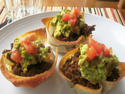 taco wonton cups topped with guacamole and tomatoes