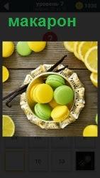 Француское кондитерское изделие макарон на тарелке и рядом нарезанный дольками лимон