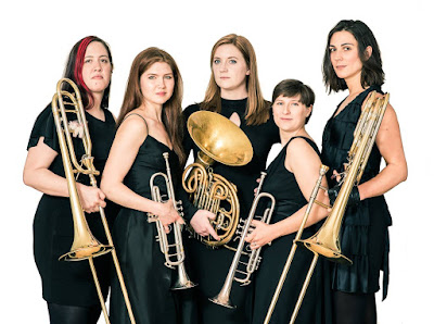 Five women in black dresses with brass instruments