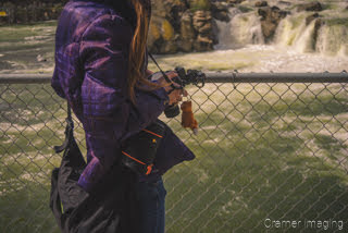 Photograph of professional landscape photographer Audrey holding a camera by a waterfall by Cramer Imaging