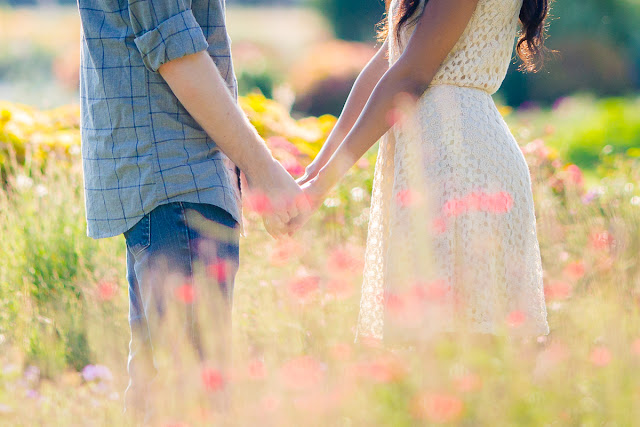 Engaged couple holding hands in a field of flowers as they will soon do on their wedding day.