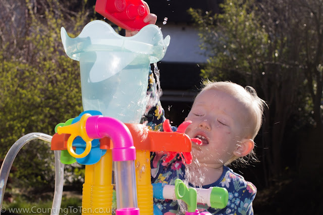 Close up of a toddler trying to pour water into a funnel and getting splashed