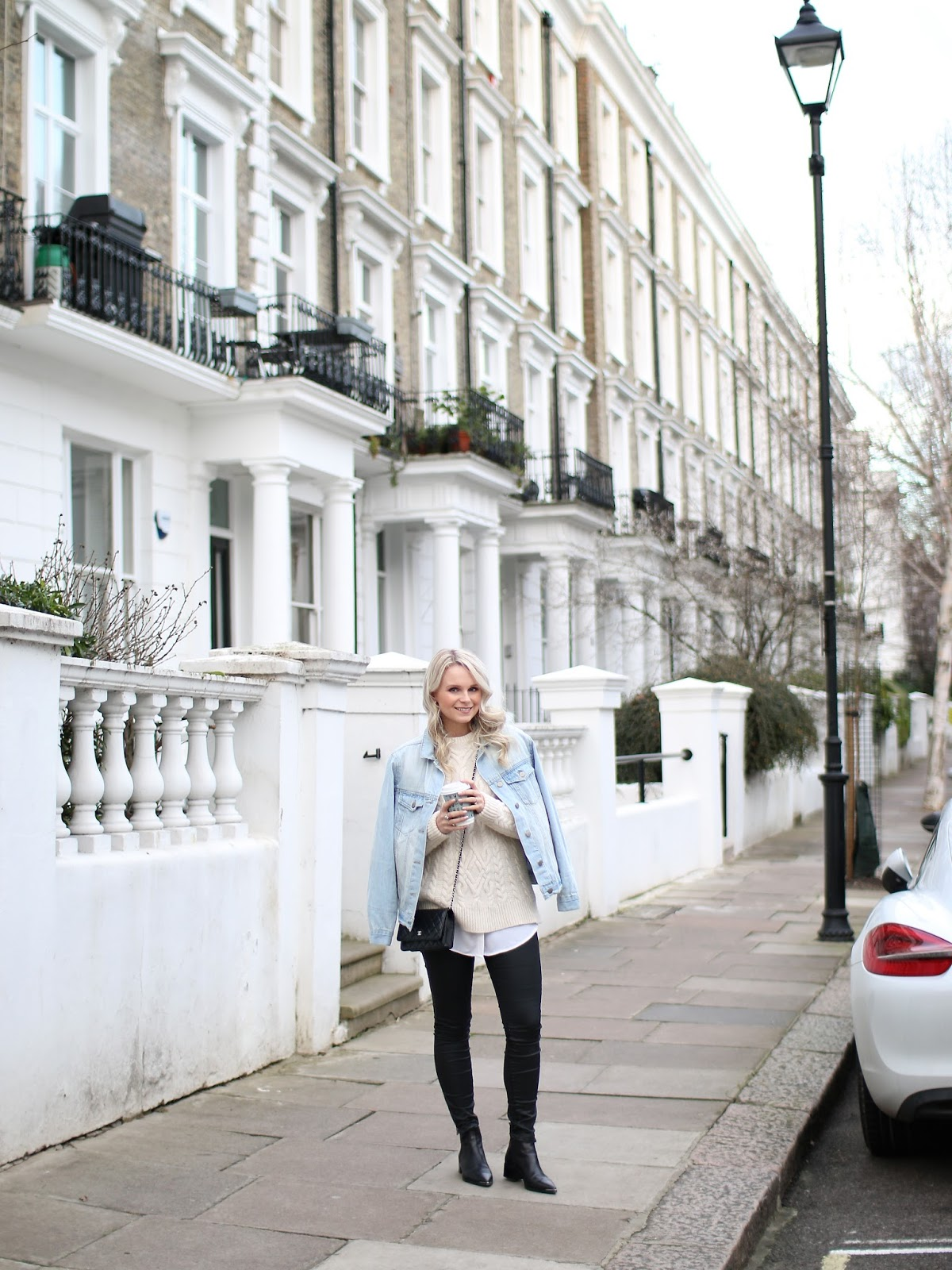 women with loose messy waved hair wearing coated denim from topshop and Acne Studio boots standing in a small street in notting hill, london