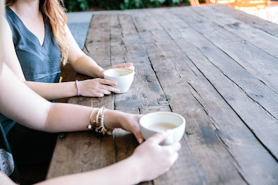 two woman sitting at a table having coffee