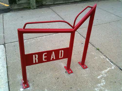 Red metal bike rack shaped like an open book with the word READ in open stencil letters