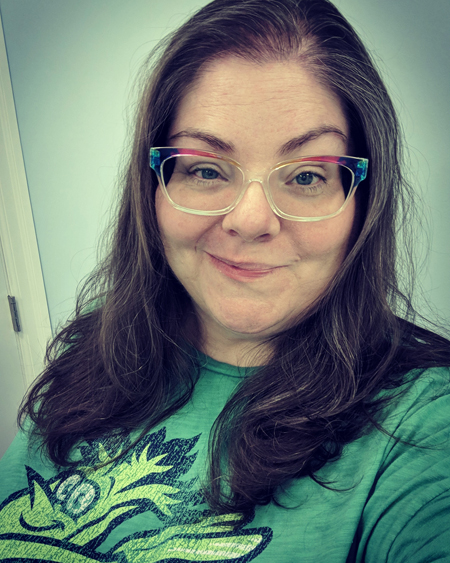 image of me from mid-chest up, wearing a green Mr. Celery t-shirt, with my hair down and wearing rainbow glasses frames