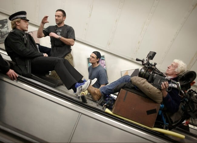 60 Iconic Behind-The-Scenes Pictures Of Actors That Underline The Difference Between Movies And Reality - Javier Bardem slides down an Underground escalator on the set of the 2012 Bond film, Skyfall.