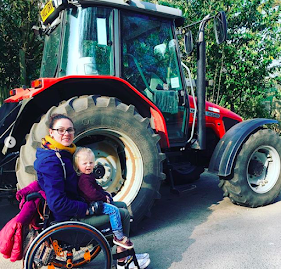 A woman in a wheelchair with a toddler on her lap sat in front of a tractor.