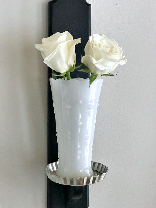 White roses in milk glass on candlestick base
