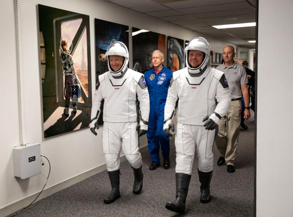 NASA astronauts Doug Hurley and Bob Behnken walk down the hallway at their Kennedy Space Center crew quarter prior to heading to LC-39A for the Demo-2 dry dress rehearsal...on May 23, 2020.