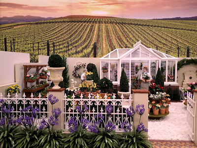One-twelfth scale miniature garden courtyard with a greenhouse,a selection of plants and flowers and two men standing at the back. Behind the garden, vineyards stretch into the distance, towards the low sun.