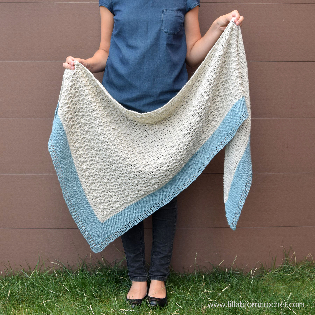 """7e74cf8ce01 Shells and Stones Shawl has an asymmetrical triangular shape with gentle  cables and bobbles placed over airy """"linen stitch"""" fabric."""