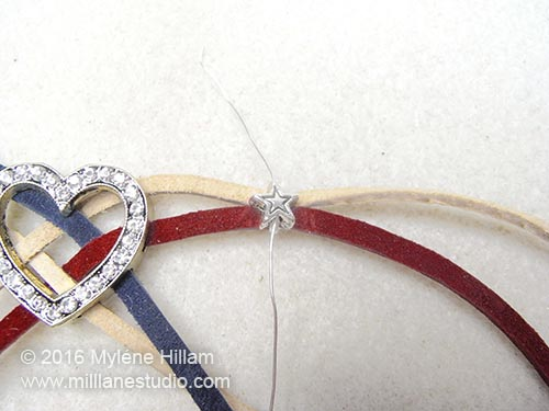A star bead is strung on the wire and sits on the laces.