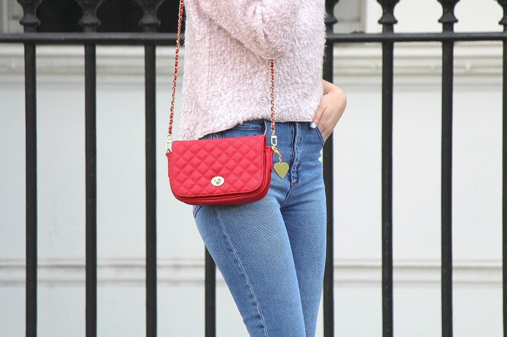 peexo fashion blogger wearing ripped mom jeans and pink fluffy jumper and red small bag in spring