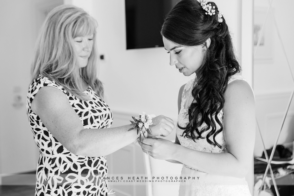 Bride putting corsage on her mother