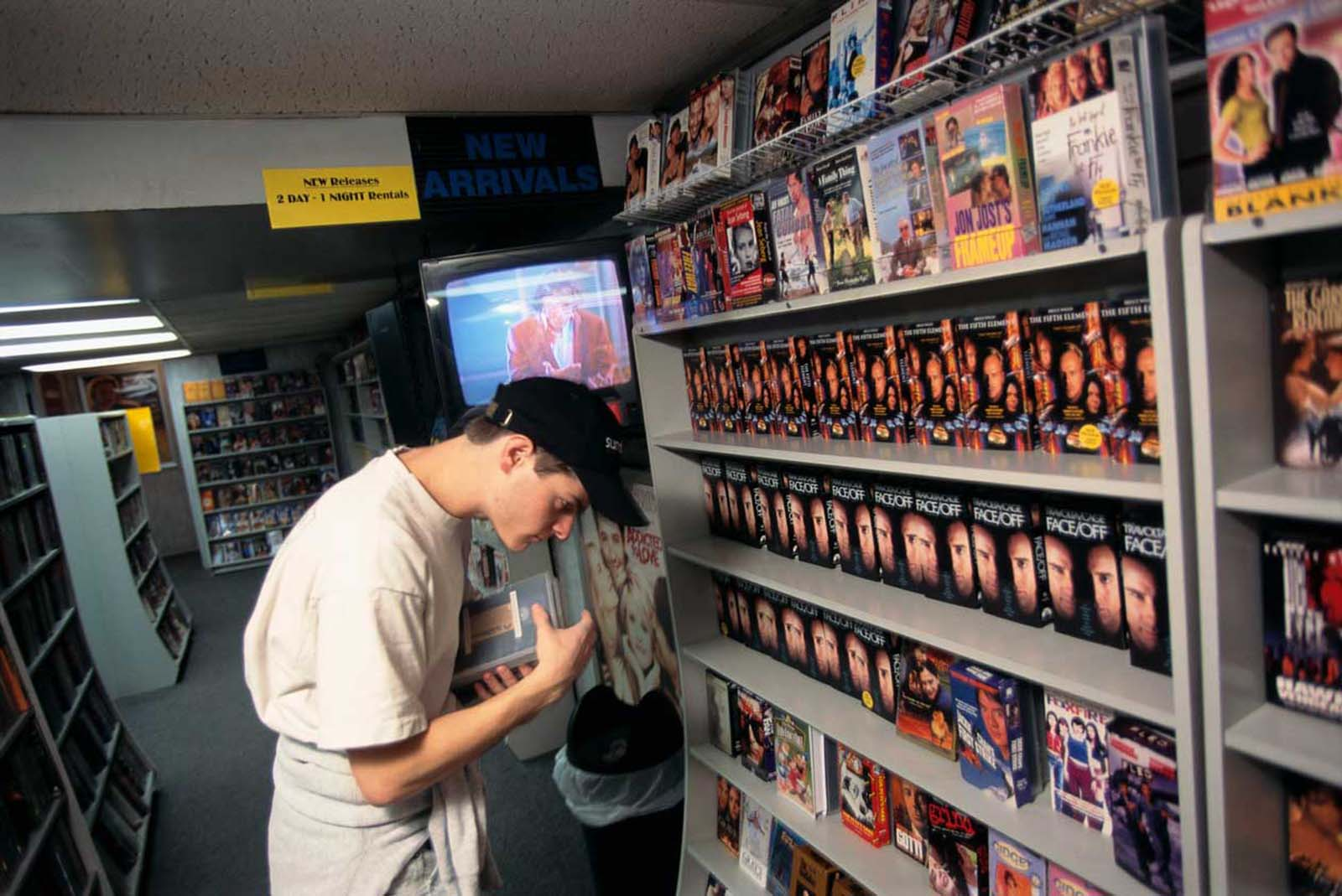 A young man looks at rental movies in Channel Video, a video store in Manhattan, New York. 1997.