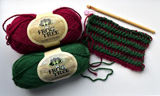 Two balls of Frog Tree Alpaca Sport yarn (red above, green below) stand to the left of a sample of the scarf.  These were the first few rows of the scarf as created during the workshop. A wooden double-ended tricot hook rests above the scarf sample.