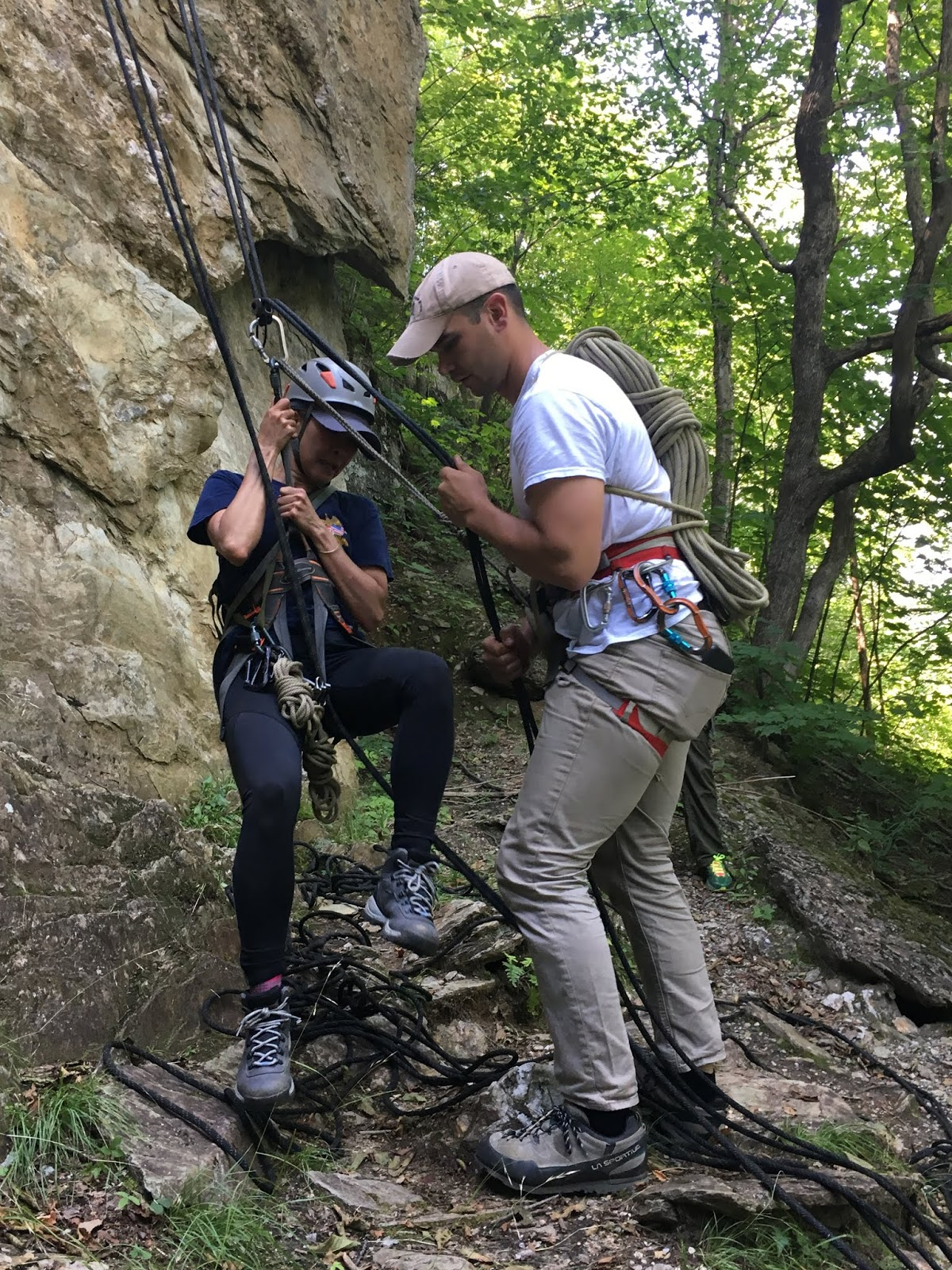 A male instructor in climbing gear unties their line from a female student who is just touching the ground following them rappelling down a cliffside.