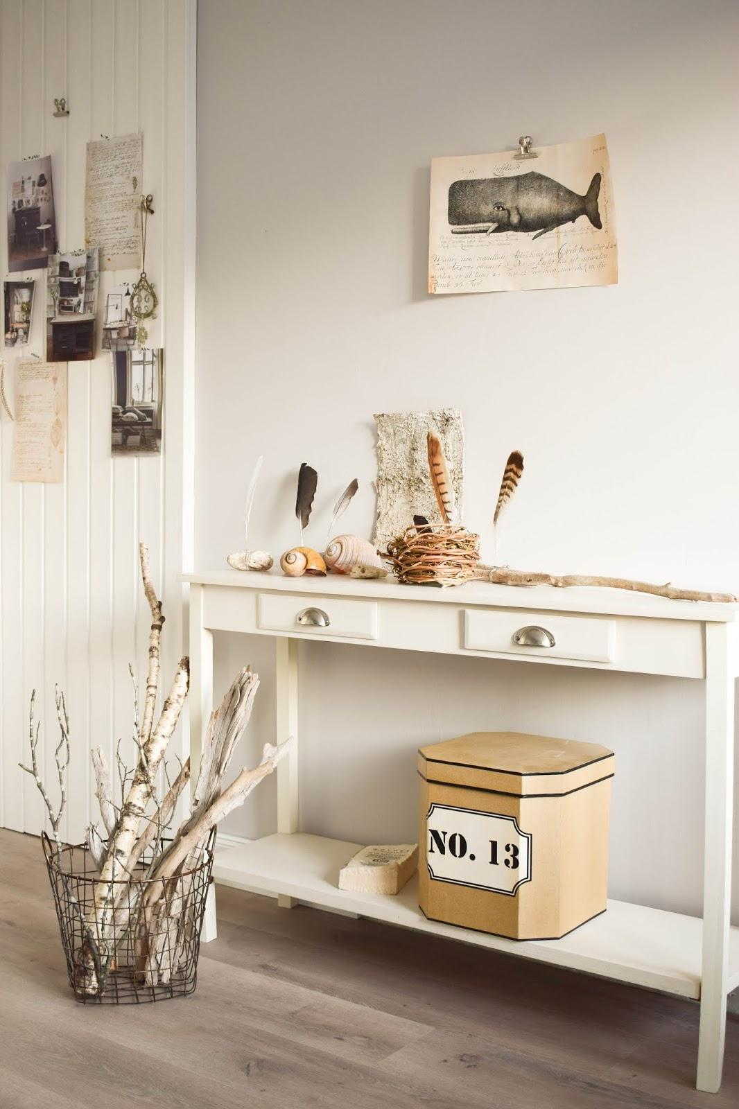Sideboard Deko weiß mit natürlichen Materialien: Federn, Schneckenhaus und Holz. Dekoidee mit Natur.