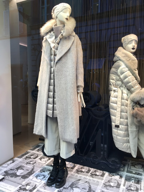 Cream coats, sweaters and pants in a Max Mara shop window in Rome.