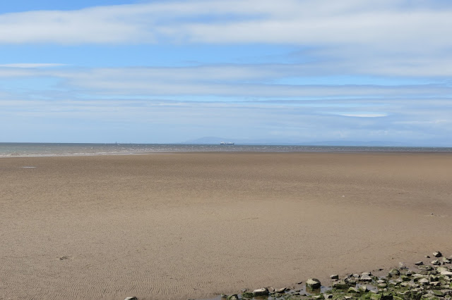 Expanse of beach with hazy outline of Lake District fells on the horizon. A ferry is in sight on the sea.