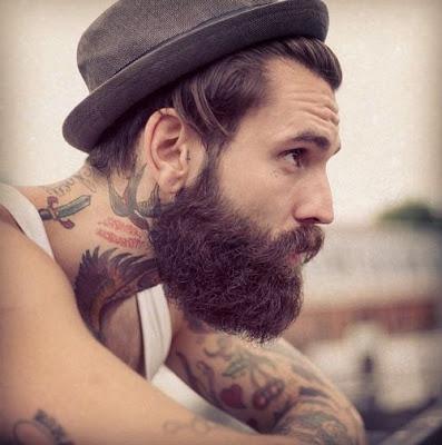Hombre con barba y sombrero mirando hacia el horizontes, lleva tatuajes tradicionales en los brazos