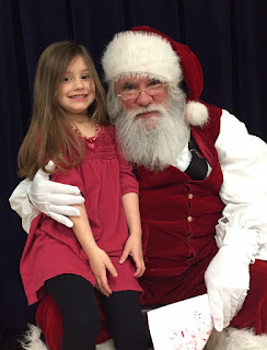 Girl in Pink dress black leggins sitting on Santa's lap