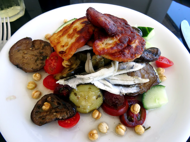 Lunch of halloumi, pickled vegetables, anchovies, tomatoes, cucumber and local sausage