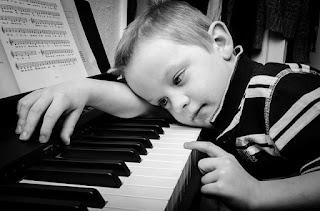 criança debruçada sobre piano