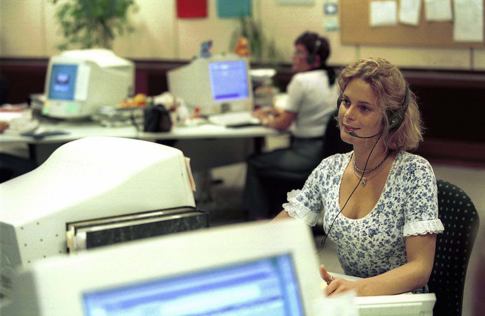 A woman in a German call centre. She wears a scoop-neck, snug, short-sleeved top with a blue floral pattern. The neckline of the top is edged with lace, as are its sleeves. Although the overall garment design implies a connection to Victorian and Edwardian women's wear, as seen in the first pictures in this piece, it actually has little in common with women's garments of a hundred years before. This woman has a thumb ring and layered 'choker' necklaces. 1999.