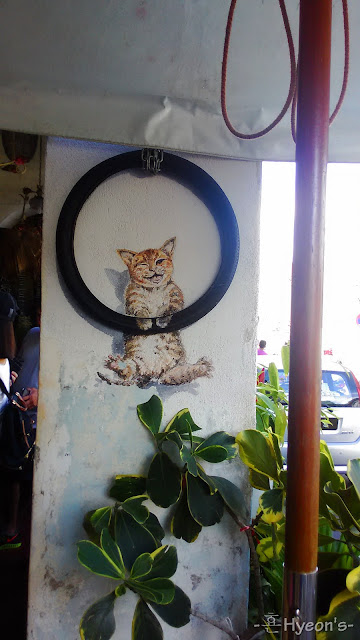 kitten hanging on the hoop street art penang