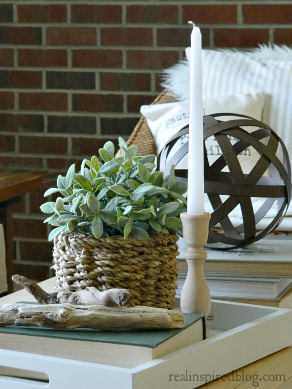 A cottage-like summer living room tour using whites, neutrals, and small pops of color in furniture and plants. wood coffee table styled with basket, plant, candle, driftwood, books, metal ball orb sphere in front of a red brick fireplace.