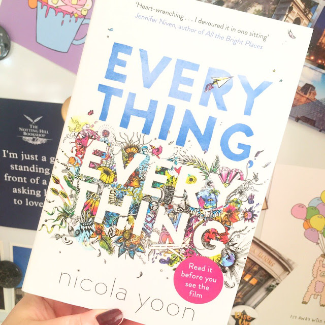 Everything, everything book held up in front of a wall of prints