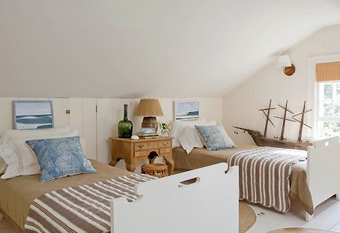 Nautical twin bedroom with white notched wood twin beds, white paneled walls, a wood night stand with a large model ship in the corner