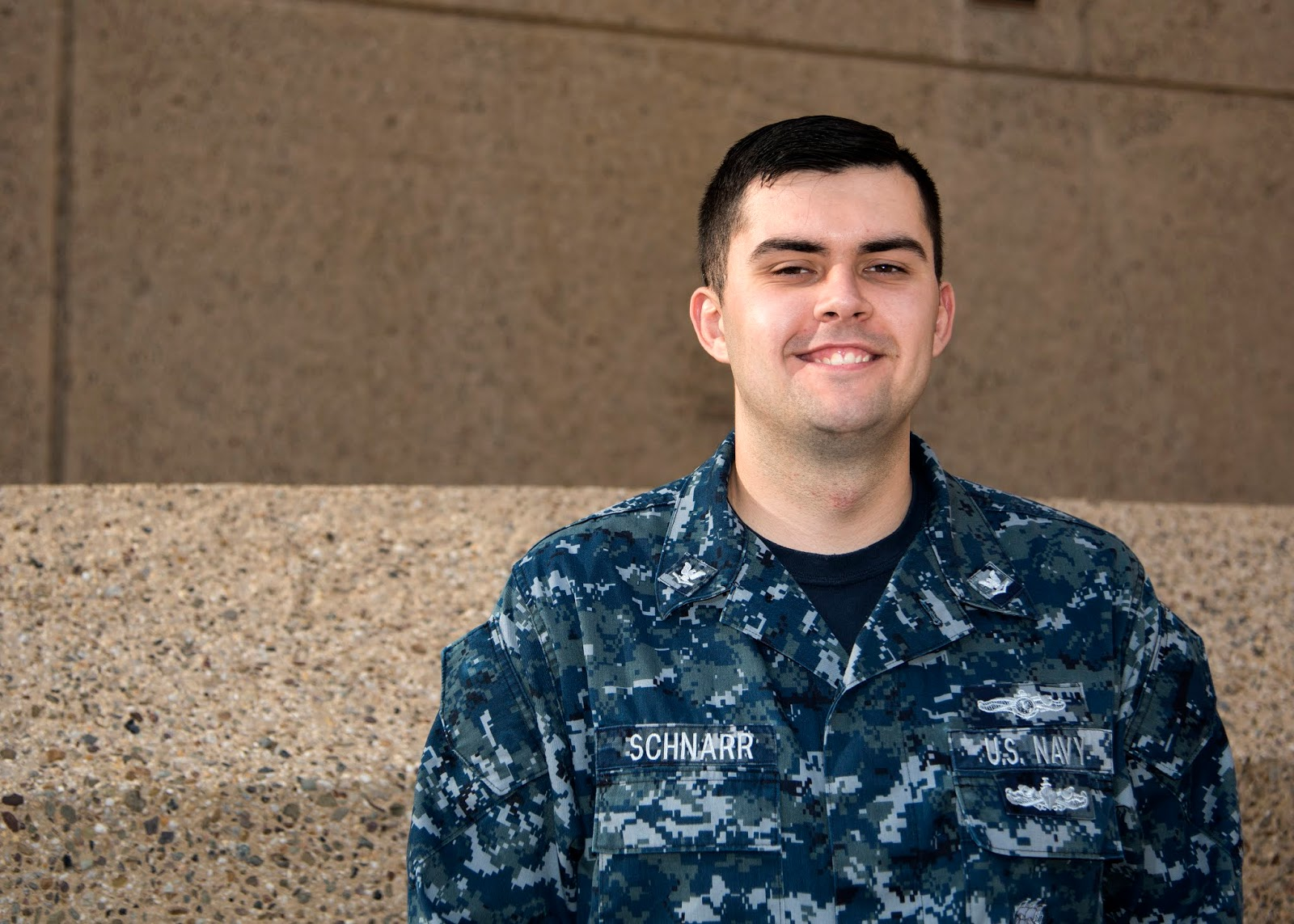 A man in a U.S. Navy uniform poses for a photo outside in front of the University logo.