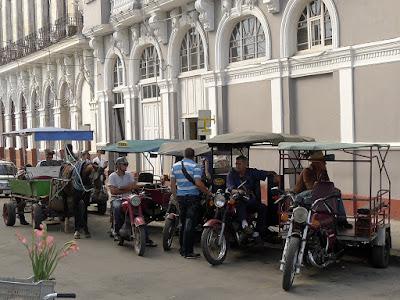 Kuba, Cienfuegos, Innenstadt, vier Motorradtaxis in Reih und Glied, außerdem ein Motoradfahrer, der sich mit ihnen unterhält, und ein Pferdefuhrwerk.