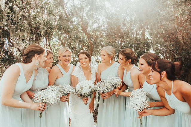 happy bridesmaids in baby blue dresses and baby breath bouquets
