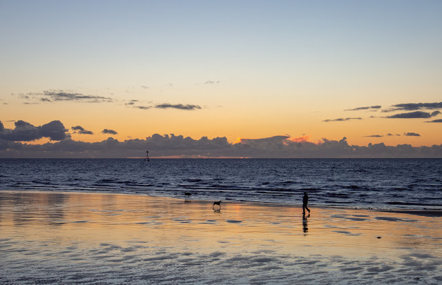 Photo of a dog walker on Maryport beach at sunset