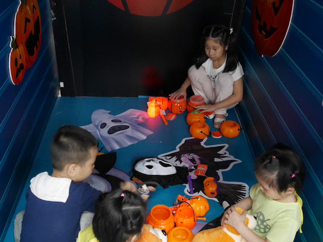 children playing with toys inside a display of Halloween items for sale at an RT-Mart in Zhongshan