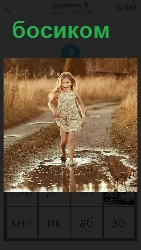 девочка бежит босиком по лужам летом на дороге