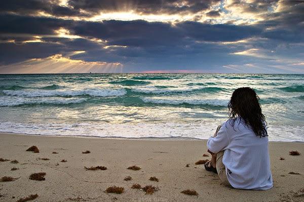 Mulher sentada sozinha na areia da praia olhando tristemente para o mar.