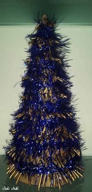 arbol de navidad macarrones con la pintura dorada y la cinta de navidad