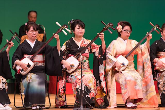 舞台で三味線を弾く女性達の写真